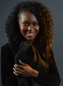 picture of a black model with curly hair holding her jacket smiling