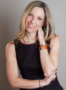 headshot of a freelance writer in black dress with her head leaning and her hand resting on her neck