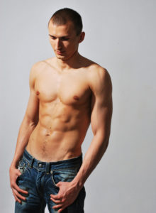 picture of a male model standing shirtless with hands on his jeans pockets