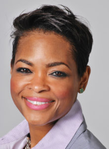 corporate headshot of a female executive in suit smiling