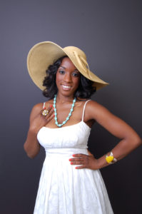 picture of a promotional model wearing a white lace dress and large brim hat and accessories smiling