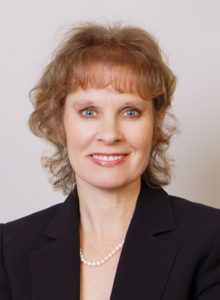 headshot of a healthcare professional in a dark suit and smile