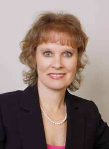professional headshot of a woman in a dark jacket and pink blouse