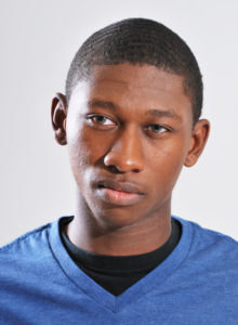 actor head shot of a teen in dc wearing a blue t-shirt thinking