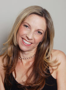author headshot of a female freelance writer in black dress with her head tilted smiling