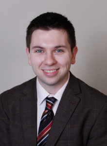 business portrait of a law student wearing a dark jacket and tie smiling