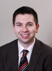 business headshot of a law student in dark jacket and tie looking at the camera smiling