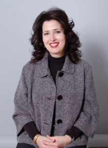 headshot of an interior designer in dark grey jacket and black sweater for promotional use