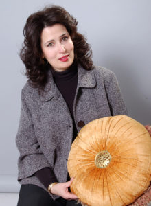promotional headshot of an interior designer in dark grey jacket showing a decorative pillow