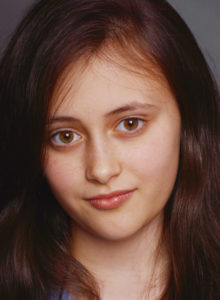 headshot of a child actress in dc looking at the camera with head tilted and a hint of a smile
