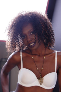 headshot of a black model with curly hair wearing a white bra in back lighting