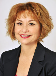 business headshot of a executive woman in dark navy suit and scarlet blouse smiling