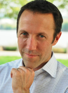 casual business headshot of a man with chin resting on his hand